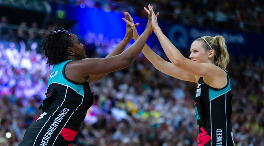 Jo Harten and Sam Wallace celebrate a goal during the Netball Australia Bushfire Relief match in Sydney's Qudos Bank Arena.